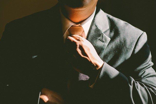 Muž v obleku upravující si kravatu